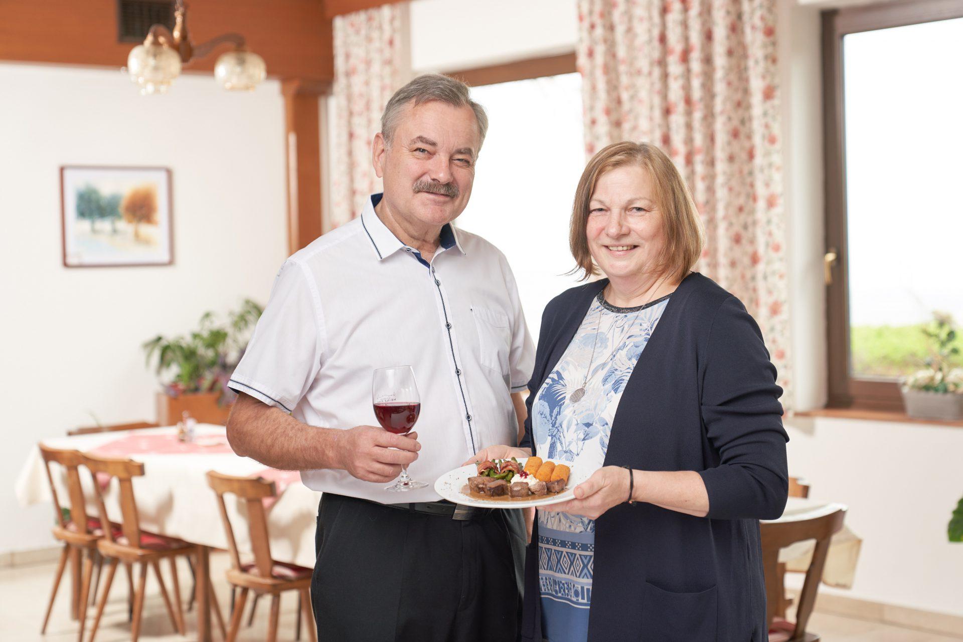 Rehmedaillons auf Gemüsewurzelsoße mit Kroketten und Speckfisolen, präsentiert von Hubert und Anneliese Osterhaus.